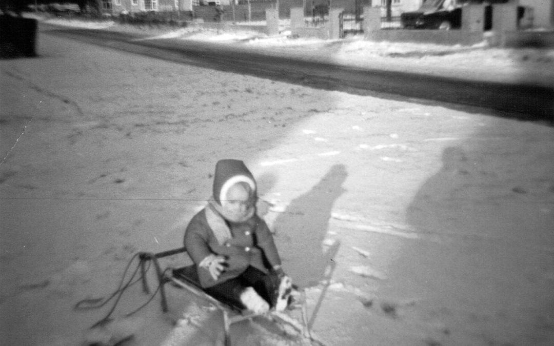 Debra Bradley sledging in Skipwith Rd with Wenlock Drive in the background – Escrick c1966