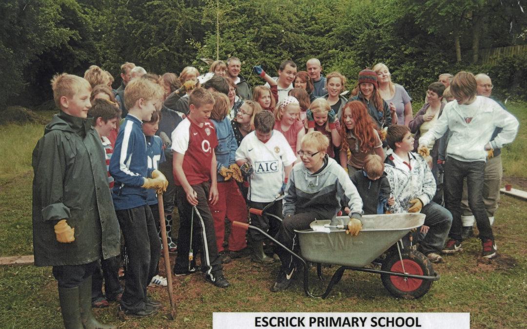 Escrick Primary School planting bulbs on the Village Green