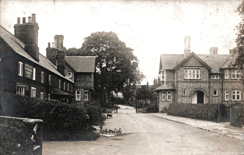Postcard of Escrick Main Street - Co-op & Water Supply Hydrant on left & Park Gates in background